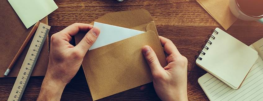 Desk with a person opening an envelope.