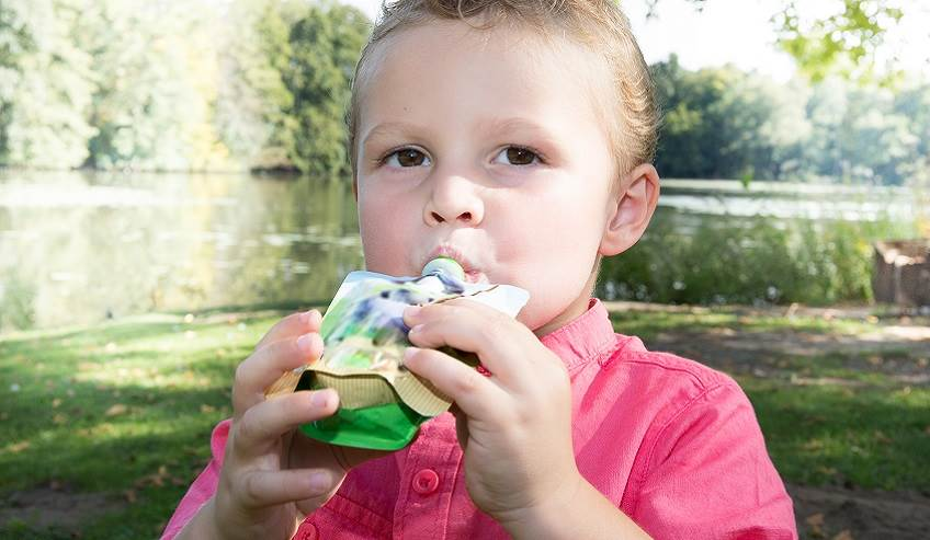 Little kid eating a food pouch with Flextra™ adhesives that are glymo-free from H.B. Fuller.
